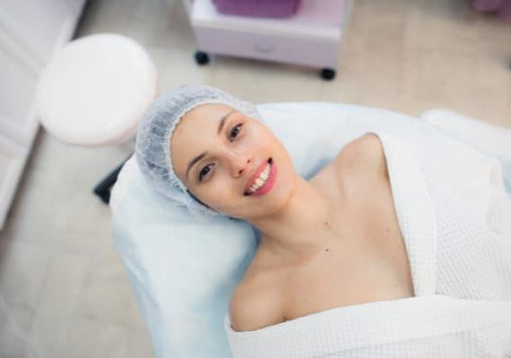 Top view of beautiful young woman getting ready for face skin treatment, lying on bed at hospital or clinic.